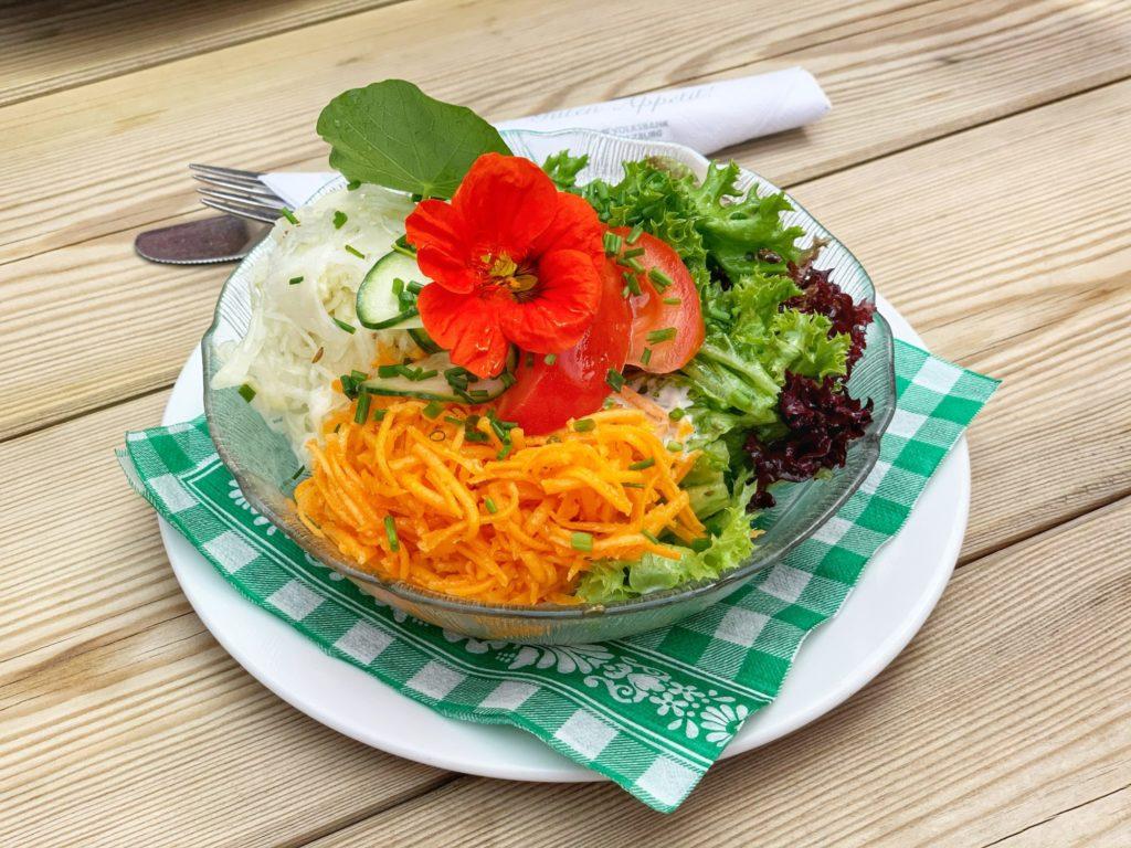 Das Foto zeigt eine Glasschüssel mit gemischtem Salat und einer roten Blüte darauf auf einer grün-karierten Serviette.