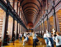 Das Foto zeigt die Bibliothek in Dublin. Man sieht viele Besucher*innen, die inmitten von dunklen Bücherregalen stehen.