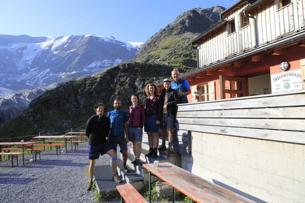 Das Projektteam der Uni Innsbruck (sechs Personen), stehen auf der Treppe einer Hütte vor einer Bergkulisse.