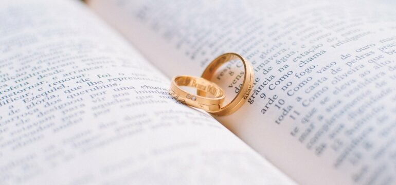 Zwei Eheringe in einem Buch.