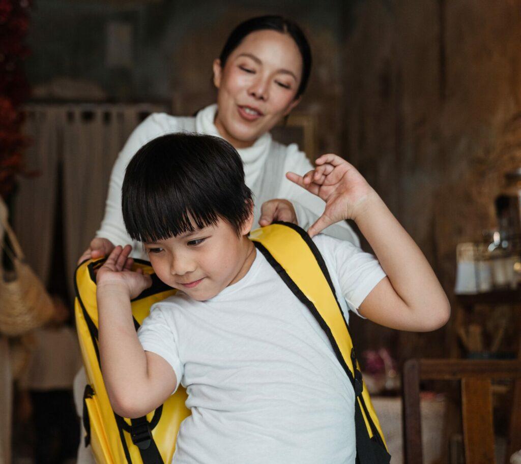 Mutter hilft Kind Schultasche anzuziehen