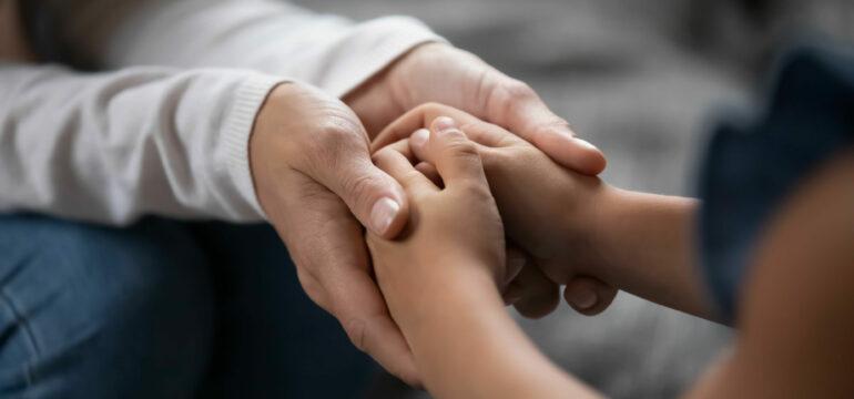 Eltern und Kind halten sich die Hände